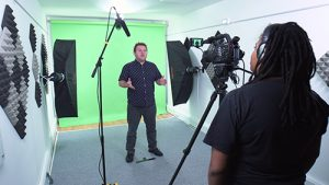 green screen studio filming vlog in a video production studio with cameraman